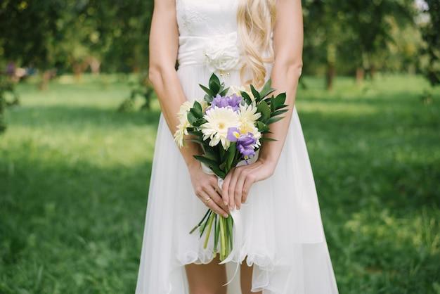 Mazzo di cerimonia nuziale delle iridi viola lilla e delle gerbere giallo-chiaro con i rami delle foglie verdi