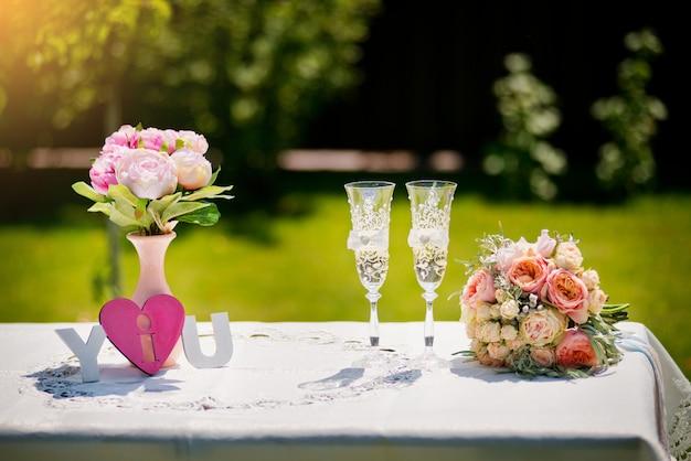 Mazzo di cerimonia nuziale e vetri del champagne sulla tabella ad una cerimonia di cerimonia nuziale