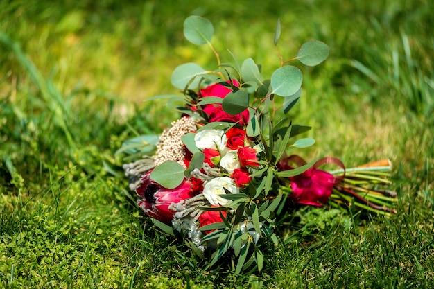 Mazzo di cerimonia nuziale su un'erba. rose luminose e nastro viola. all'aperto. avvicinamento.