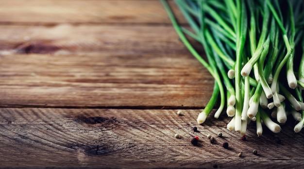 Mazzo di cipolle verdi organiche fresche, scalogno su legno con pepe.