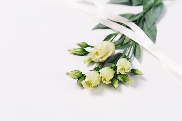 Mazzo di eustoma bianco su fondo bianco leggero con lo spazio della copia. cartolina d'auguri floreale per invito o congratulazioni.