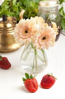 Mazzo di fiore della gerbera con il piatto delle fragole