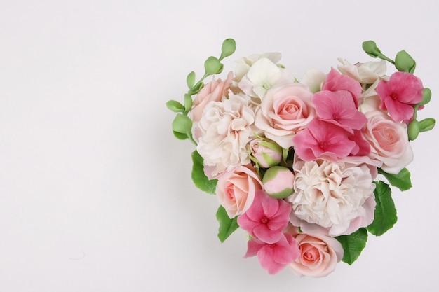 Mazzo di fiori a forma di cuore su una superficie bianca. . san valentino, concetto di matrimonio.
