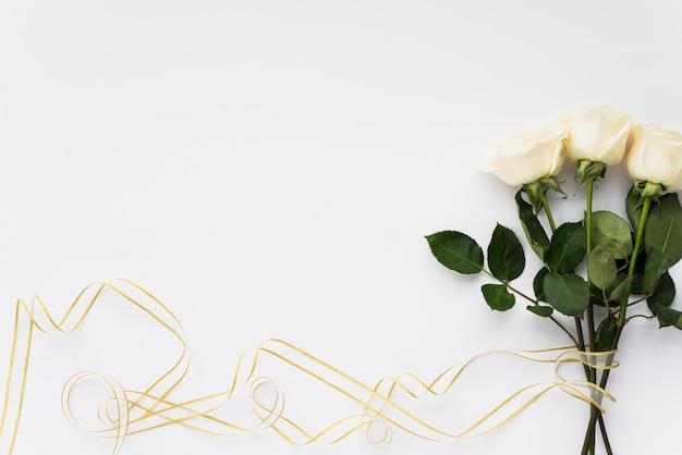 Mazzo di fiori bianchi e nastro su sfondo chiaro