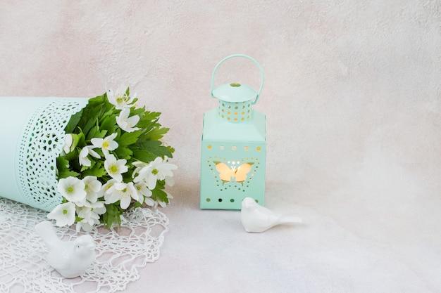 Mazzo di fiori bianchi in un vaso, figure di uccelli e un candeliere con candela