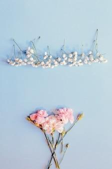Mazzo di fiori di garofano e fiori gypsophila disposti su sfondo chiaro