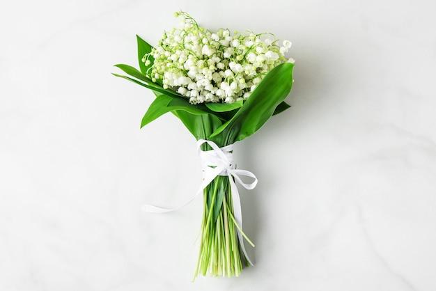 Mazzo di fiori di mughetto su marmo bianco. disteso. vista dall'alto