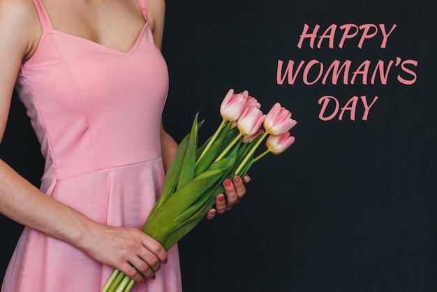 Mazzo di fiori di tulipani rosa nelle mani di una ragazza. cartolina d'auguri con testo felice festa della donna