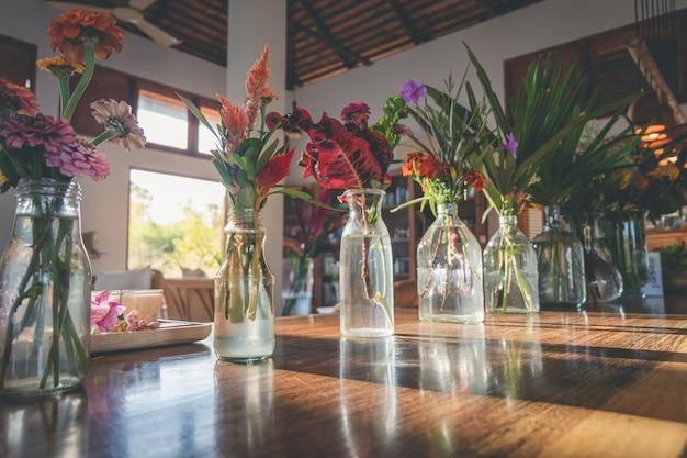 Mazzo di fiori e foglie nel vaso sul tavolo di legno