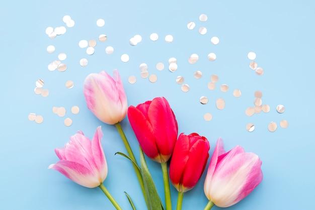 Mazzo di fiori freschi luminosi diversi vicino coriandoli