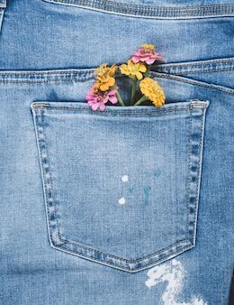Mazzo di fiori nella tasca posteriore dei blue jeans
