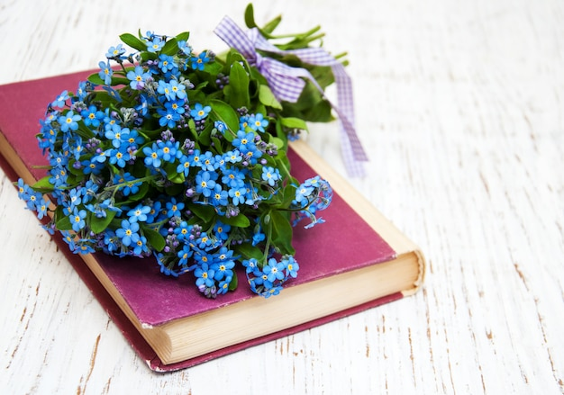 Mazzo di fiori nontiscordardime e vecchio libro