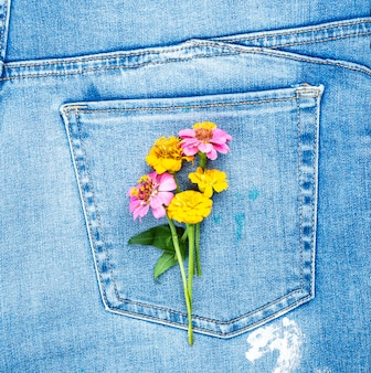 Mazzo di fiori sulla tasca posteriore dei blue jeans