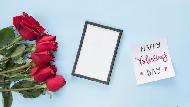 Mazzo di fiori vicino a carta con titolo e cornice per foto