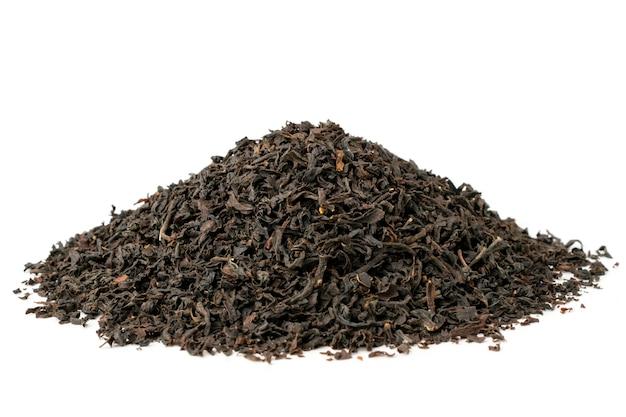 Mazzo di foglie di tè nero secco su bianco, primi piani.