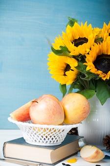 Mazzo di girasoli in vaso bianco con mele