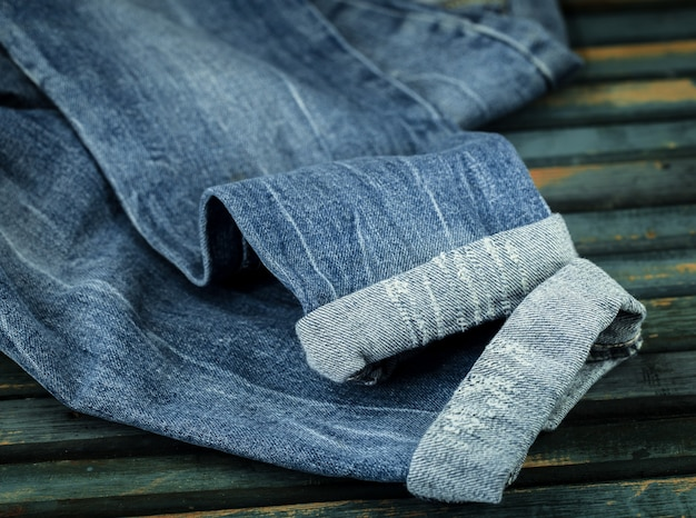 Mazzo di jeans su uno sfondo di legno cosparso di jeans, close-up, vestiti alla moda