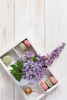 Mazzo di lillà fragrante fresco in tazza bianca e biscotti deliziosi dei maccheroni in scatola