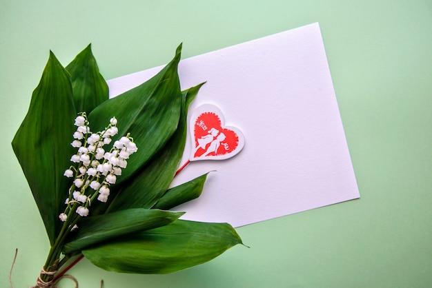 Mazzo di mughetti, un cuore e un foglio di carta