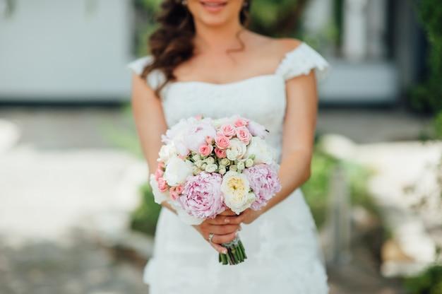 Mazzo di nozze della tenuta della sposa su cerimonia