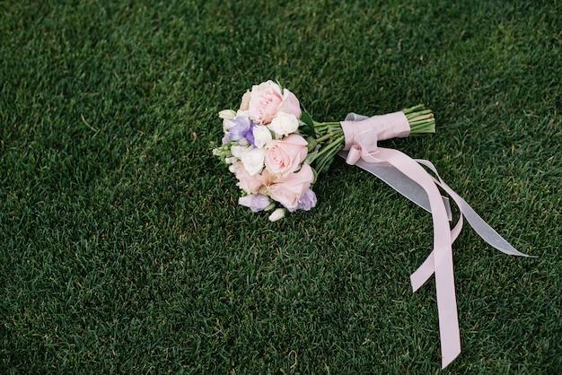 Mazzo di nozze delle rose rosa e bianche che si trovano sull'erba