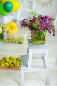 Mazzo di paesaggio dei fiori su una sedia con frutta su un fondo vago