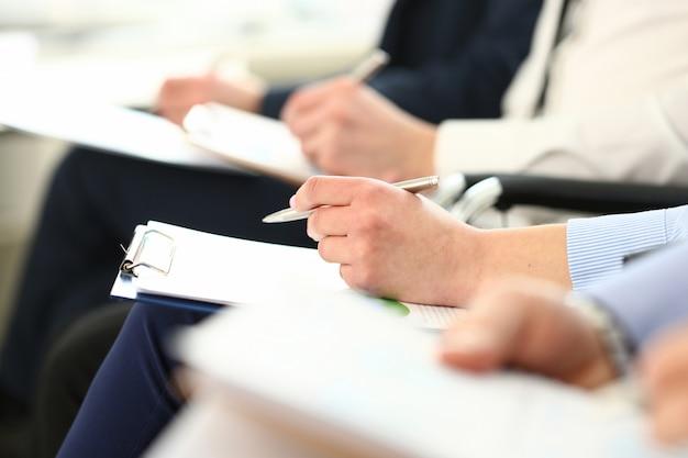 Mazzo di persone sedute in coda con appunti e penne che prendono appunti