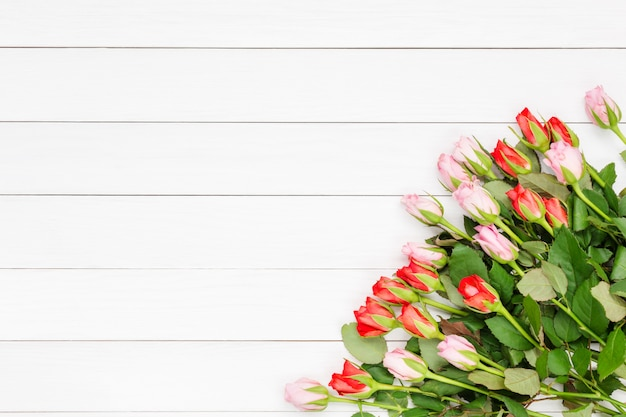 Mazzo di piccole rose su fondo di legno bianco. vista dall'alto, copia spazio
