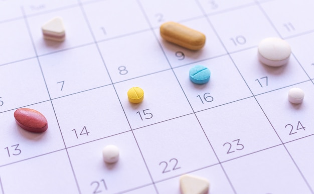 Mazzo di pillole differenti su una priorità bassa del calendario. concetto di assistenza sanitaria