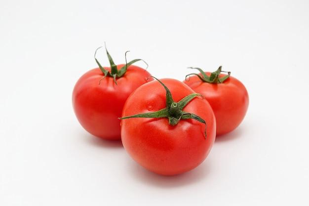 Mazzo di pomodori maturi isolati su fondo bianco