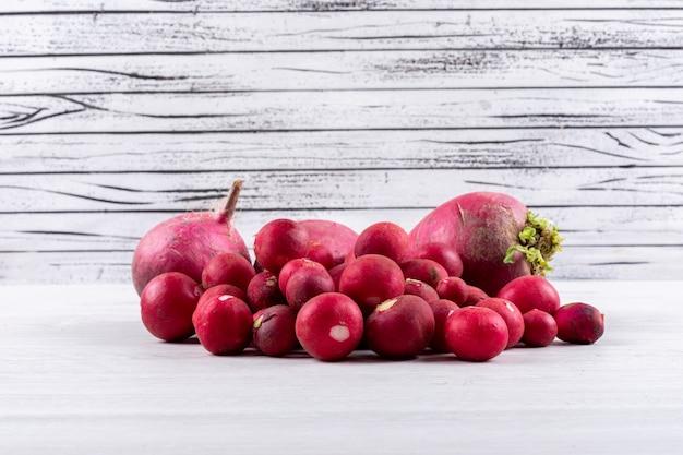 Mazzo di ravanelli freschi rossi su una tavola bianca e di legno. vista laterale.