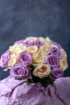 Mazzo di rose bianche e viola sorprendenti fresche in carta del mestiere su superficie scura per cartolina, copertina, banner. bellissimi fiori come regalo per la mamma, il compleanno o il matrimonio. copia spazio