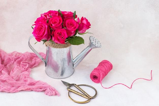 Mazzo di rose rosa in un annaffiatoio, filo e forbici