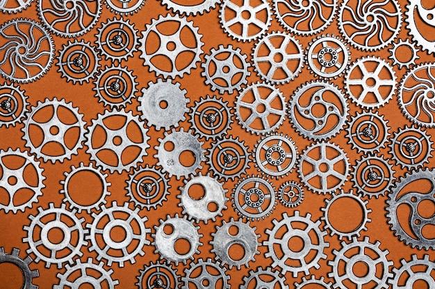 Mazzo di ruote dentate su uno sfondo arancione.