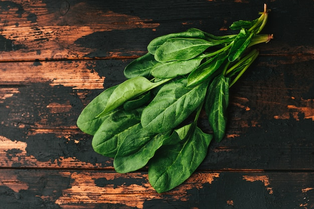 Mazzo di spinaci freschi su una tavola di legno scura