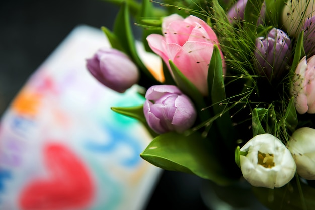 Mazzo di tulipani e disegno per la mamma sullo sfondo
