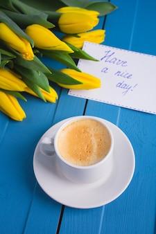 Mazzo di tulipani gialli e un caffè della tazza