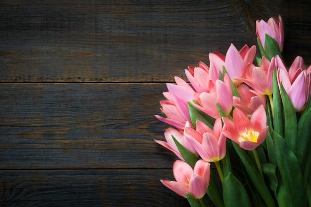 Mazzo di tulipani rosa su fondo scuro in legno