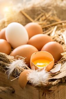 Mazzo di uova marroni fresche in una cassa di legno