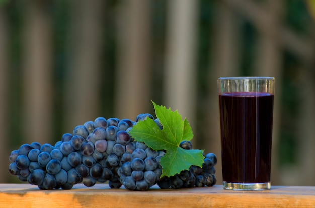Mazzo di uva blu e un bicchiere di succo d'uva sul tavolo nel giardino