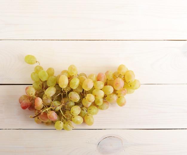 Mazzo di uva verde su superficie di legno con