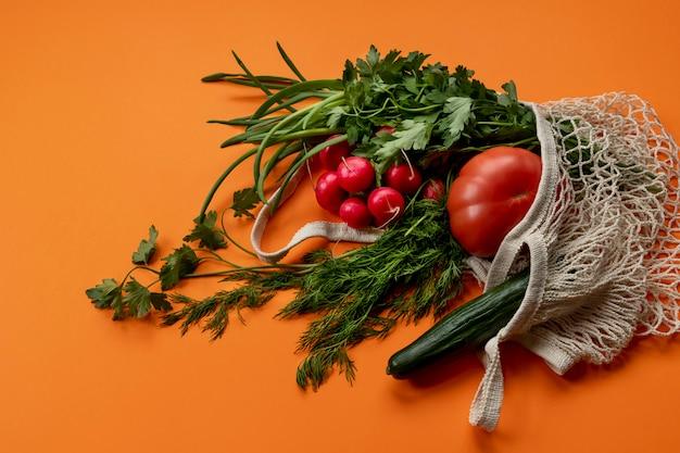 Mazzo di verdure: cipolla verde, prezzemolo, aneto, ravanelli, pomodoro in un sacchetto di stringa di rete riutilizzabile in cotone leggero