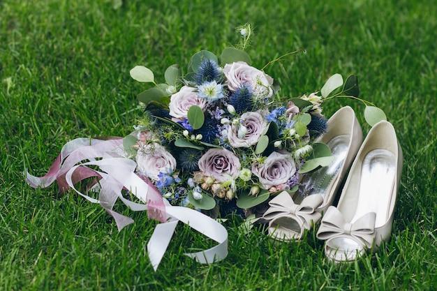 Mazzo e scarpe della sposa sull'erba