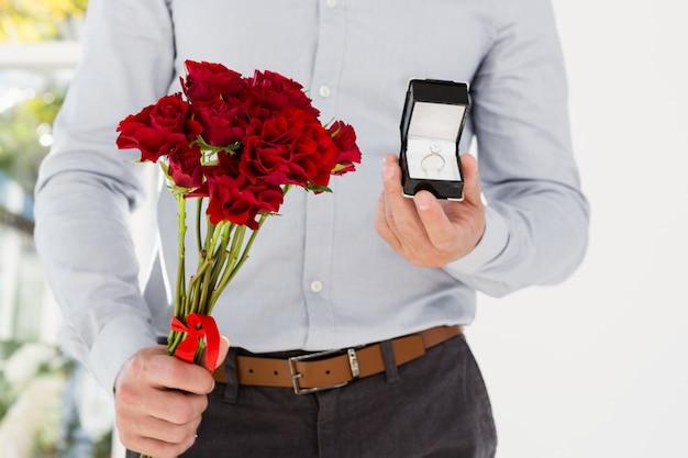 Mazzo felice dell'anello di fidanzamento e del fiore della tenuta del giovane