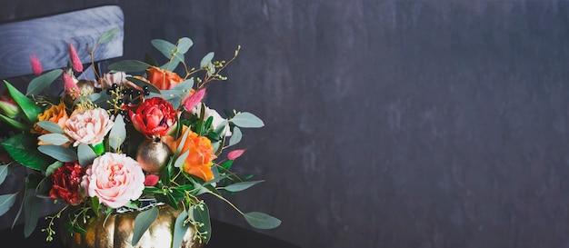Mazzo floreale di autunno in vaso di punpkin sulla sedia nera, banner