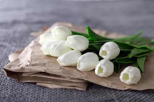 Mazzo fresco di tulipani bianchi su carta riciclata su sfondo grigio
