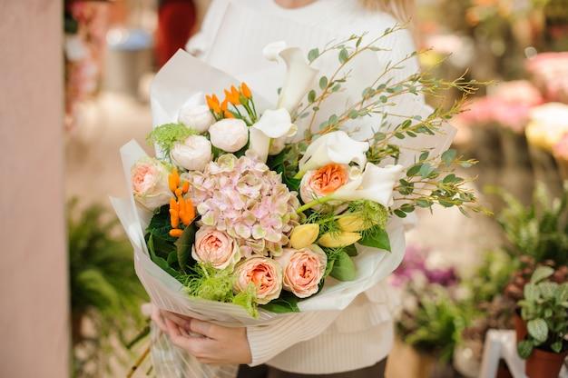 Mazzo multicolore stupefacente del biglietto di s. valentino dei fiori in mani femminili
