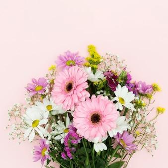 Mazzo piano dei fiori di disposizione su fondo rosa