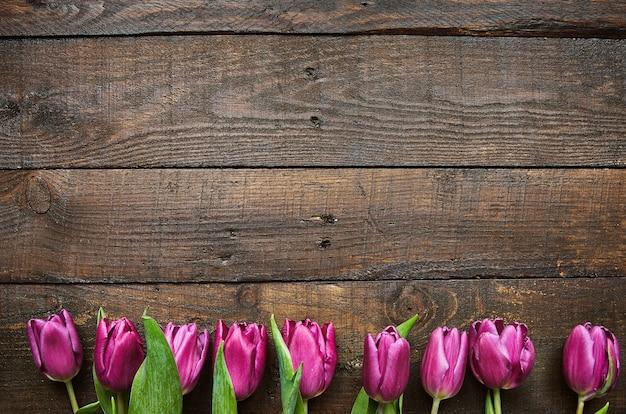 Mazzo rosa e tulipani sul fondo di legno delle plance del granaio scuro. spazio per testo, copia, lettere. modello di cartolina.