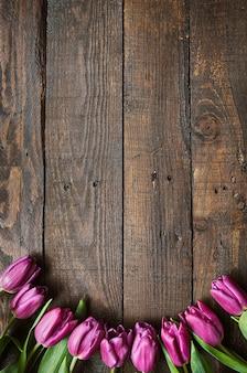 Mazzo rosa e tulipani sul fondo di legno delle plance del granaio scuro